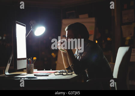 Businessman drinking coffee at night - Stock Photo