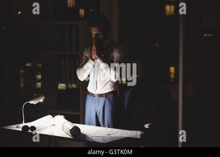 Overworked businessman working at night - Stock Photo