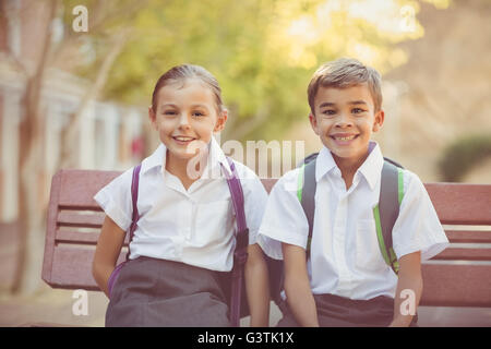 Portrait of smiling school kids sitting on bench - Stock Photo