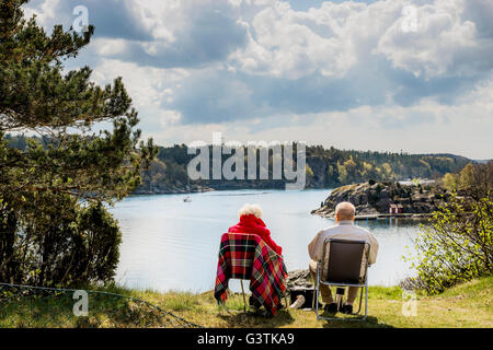 Sweden, West Coast, Bohuslan, Senior couple sitting on lounge chairs and looking at view - Stock Photo