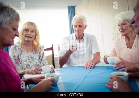 Group of seniors drinking coffee - Stock Photo