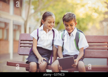 Happy school kids sitting on bench and using digital tablet - Stock Photo