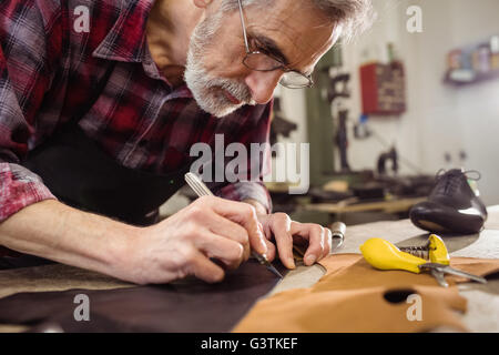 Close up of concentrated cobbler working - Stock Photo