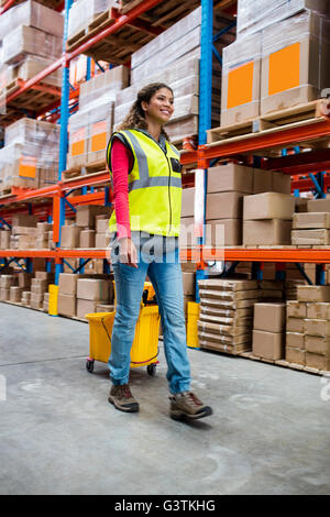 Happy woman pushing warehouse floor - Stock Photo