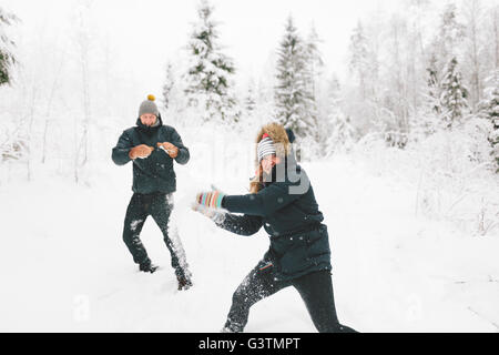 Finland, Jyvaskyla, Saakoski, Young couple having snowball fight - Stock Photo