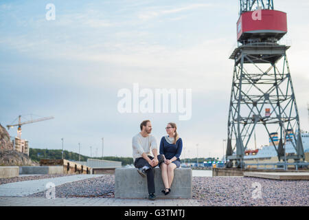 Finland, Varsinais-Suomi, Turku, Couple sitting on block and talking at construction site - Stock Photo