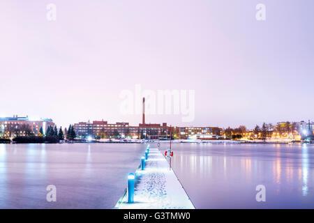 Finland, Pirkanmaa, Tampere, Pyhajarvi, Illuminated pier over lake at dusk - Stock Photo
