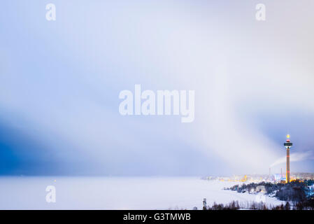 Finland, Pirkanmaa, Tampere, Nasijarvi, Illuminated communications tower over city by lake at dusk - Stock Photo