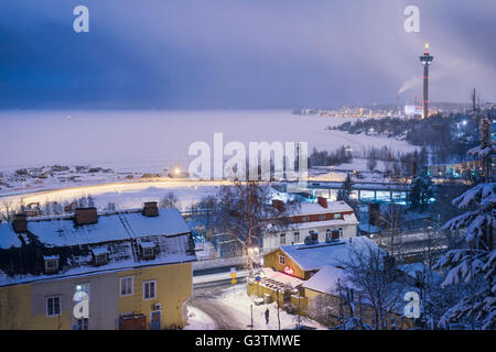 Finland, Pirkanmaa, Tampere, Nasijarvi, Illuminated cityscape with frozen lake in background - Stock Photo