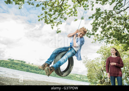 A girl and a boy playing on a tyre hanging from a tree on the shore beside Bala Lake in Wales. - Stock Photo