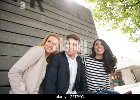 Three friends sitting on a bench on the South Bank in London. - Stock Photo
