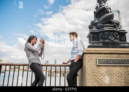 A young couple taking photographs on the South Bank in London. - Stock Photo
