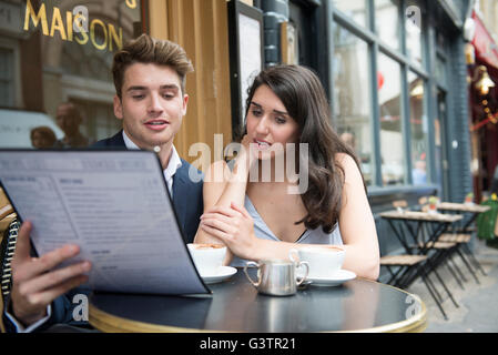 Young couple looking at menu outside typical english tea for Cafe du jardin covent garden