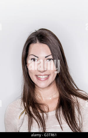 A young woman posing in a studio looking happy. - Stock Photo