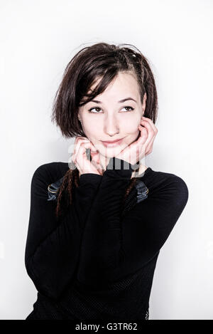 A young woman posing in a studio looking distracted. - Stock Photo