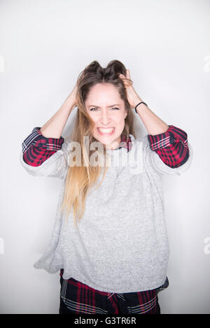 An attractive young woman posing in a studio looking frustrated. - Stock Photo