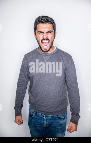 A young man posing in a studio looking angry. - Stock Photo