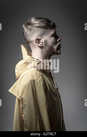 Studio portrait of a bearded young man in a yellow wind cheater. - Stock Photo