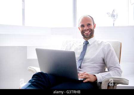 A professional man sitting making notes on a laptop in a business environment. - Stock Photo