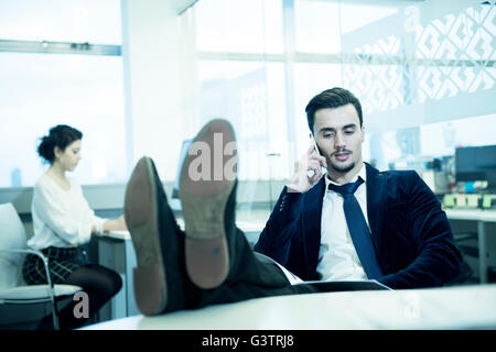 A professional man making a phone call in an office environment. - Stock Photo