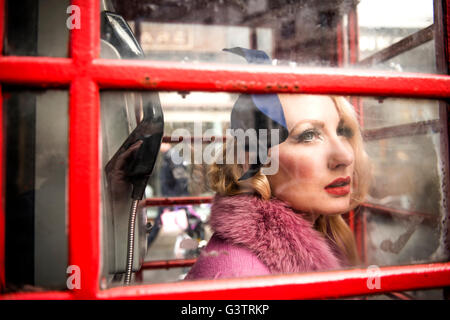 A stylish young woman dressed in 1930s style clothing standing in a traditional telephone kiosk on a London street. - Stock Photo