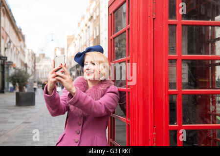 A stylish young woman dressed in 1930s style clothing taking a selfie outside a traditional telephone kiosk on a - Stock Photo