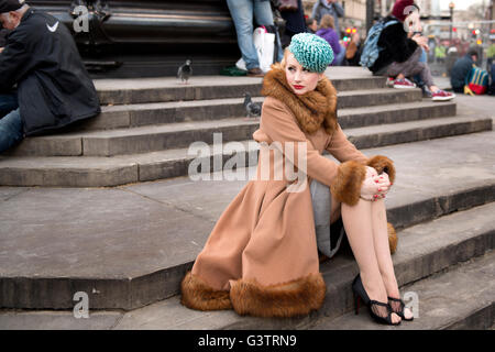 A stylish young woman dressed in 1930s style clothing sitting by the statue of Eros at Piccadilly Circus. - Stock Photo