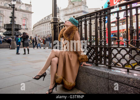 A stylish young woman dressed in 1930s style clothing sitting smoking by railings at the entrance to Piccadilly - Stock Photo