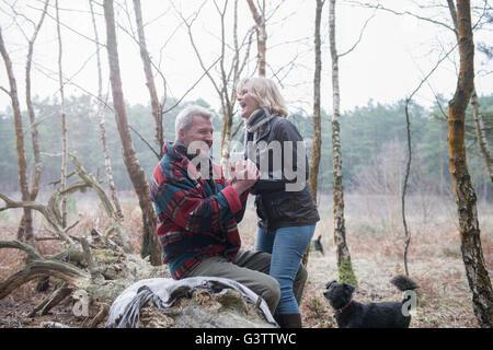 Senior couple enjoying a break with their dog during a woodland walk. - Stock Photo