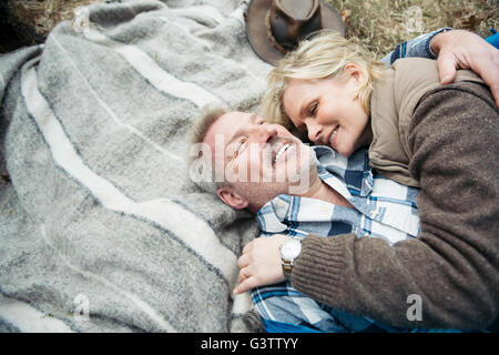 Senior couple cuddling together on a blanket at their campsite. - Stock Photo