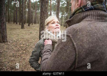 Senior couple enjoying a break during a woodland walk. - Stock Photo