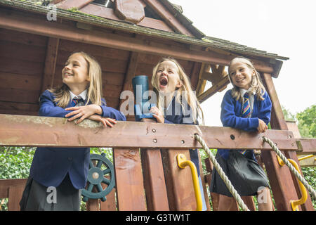 Three girls in school uniform stand together on wooden playground apparatus. - Stock Photo
