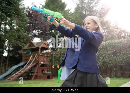 A ten year old girl in school uniform firing two water pistols. - Stock Photo