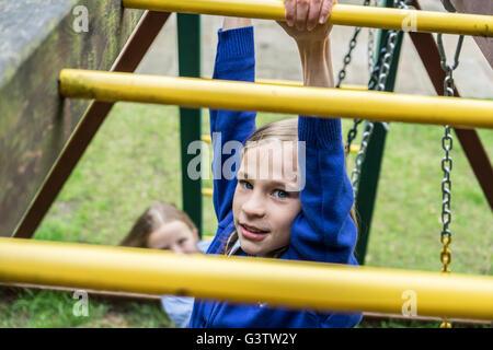A ten year old girl in school uniform climbing on playground apparatus. - Stock Photo