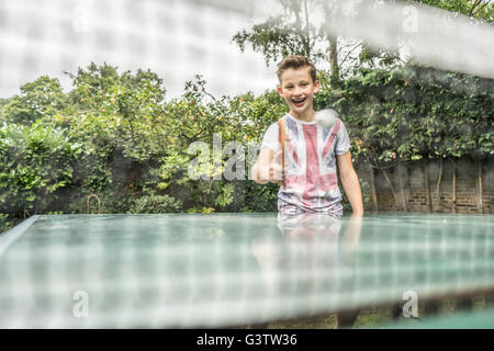 A twelve year old boy playing table tennis outside. - Stock Photo