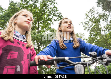 Looking up at two girls playing on a bicycle outside. - Stock Photo
