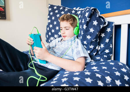 A ten year old boy laying on a bed listening to music on earphones. - Stock Photo