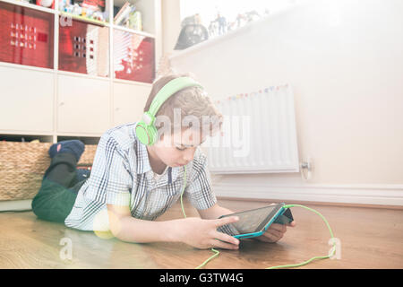 A ten year old boy laying on the floor listening to music on earphones. - Stock Photo