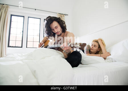 A cool young tattooed couple laying on a bed with a guitar. - Stock Photo