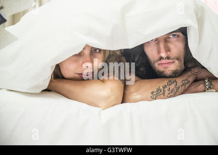 A cool young tattooed couple peeking out from under a duvet on a bed. - Stock Photo
