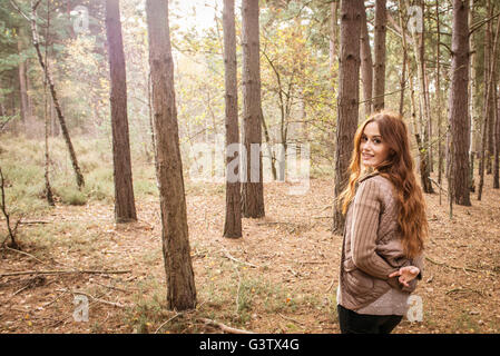 A young woman communing with nature in a forest in Autumn. - Stock Photo