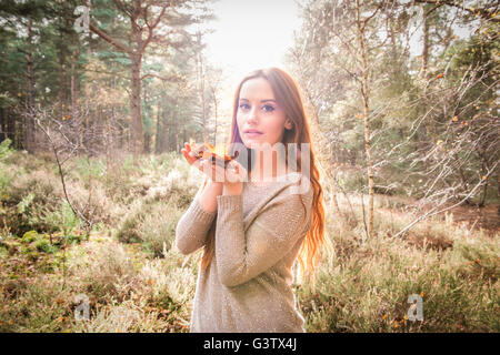 A young woman standing with a handful of leaves in a forest in Autumn. - Stock Photo