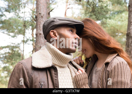 A young couple enjoying a forest walk in Autumn. - Stock Photo