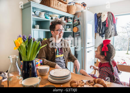A father sits in his kitchen chatting to his 6 year old daughter. - Stock Photo