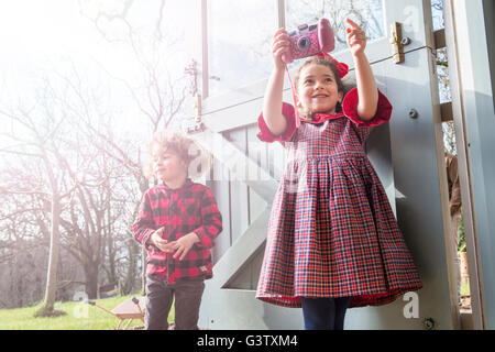 A six year old girl standing with her brother at a back door taking pictures with a toy camera. - Stock Photo