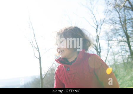 A four year old boy in a red jumper standing in the sunshine in a garden. - Stock Photo