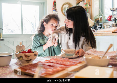 A six year old girl being comforted by her mother at the dinner table. - Stock Photo