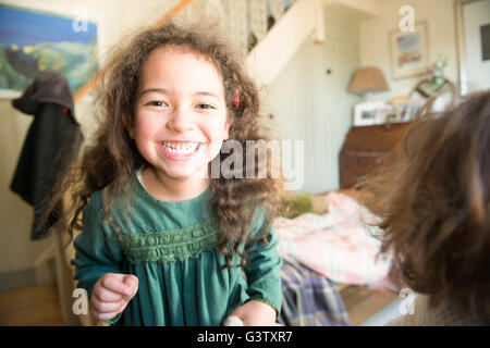 A six year old girl in a green dress stands in a room smiling at the camera. - Stock Photo