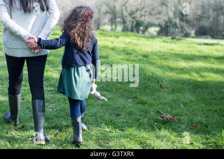 A mother and six year old daughter enjoying being out in the garden on an early Spring day. - Stock Photo