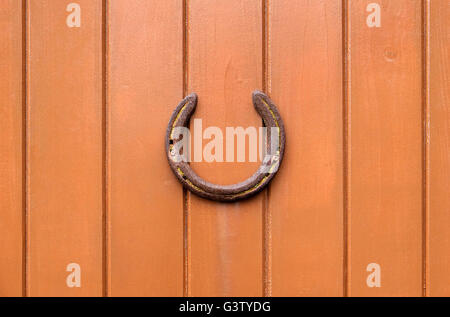 old horseshoe on brown painted timber wooden wall - Stock Photo